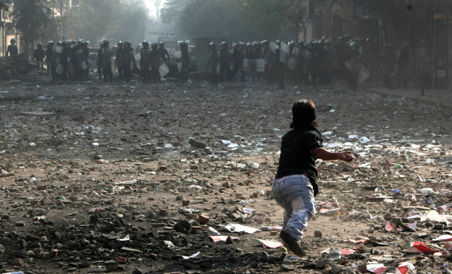 4-1-STANDALONE-An-Egyptian-protester-throws-a-rock-during-clashes-with-riot-police-along-a-road-near-Tahrir-Square-in-Cairo-on-November-23-2011.